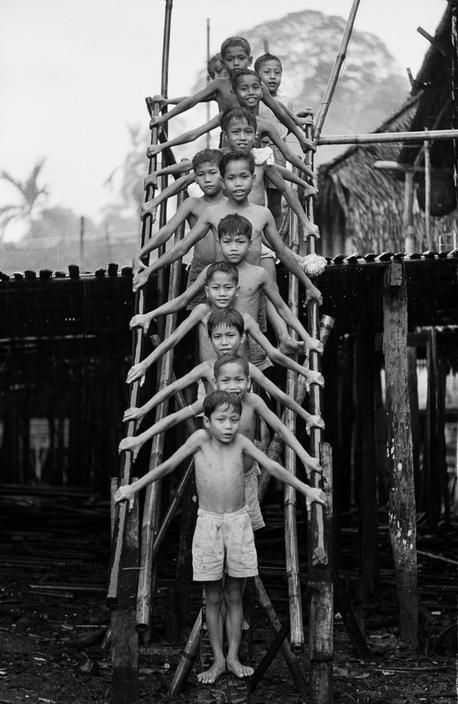 Thomas Hoepker - Children of the Iban tribe stand on a ladder to their longhouse. Sarawak on Borneo. 1964. S)