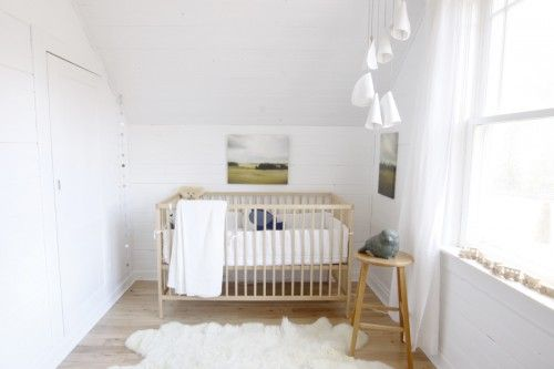 """: """"We kept the nursery minimal and light so we could add colour and update the space throughout Sebastian's childhood with accessories and artwork. The crib is IKEA. The blue bird pillow in the crib is handmade from salvaged wool by Three Bad Seeds. The artwork is an older landscape series from Walter Helena Photography. Sebastian loves anything shiny and sparkly – his favourite thing is to stare the disco ball above his changing table."""