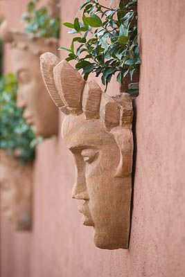 Marvelous AFRICAN GARDEN, PROVENCE, FRANCE: DESIGNER DOMINIQUE LAFOURCADE: TERRACOTTA  MASKS ON WALL