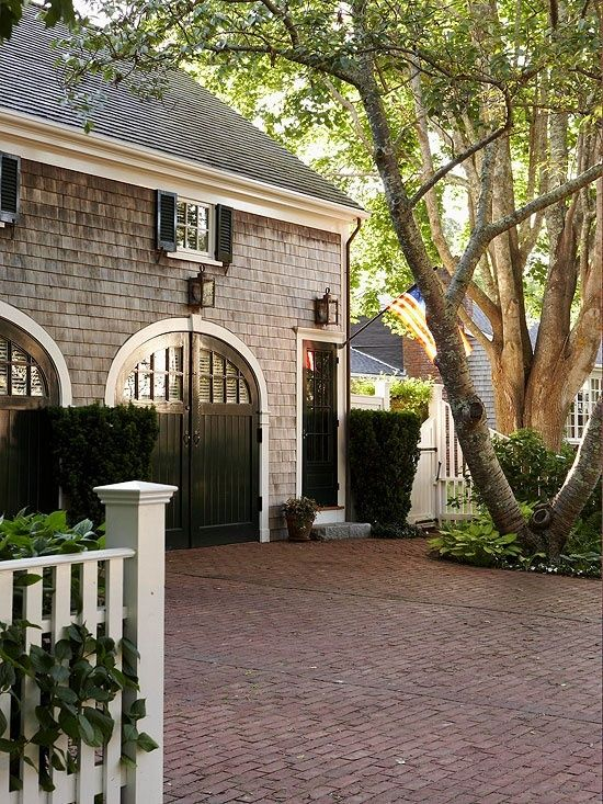 Brick driveway, carriage house doors, shingle siding, lanterns