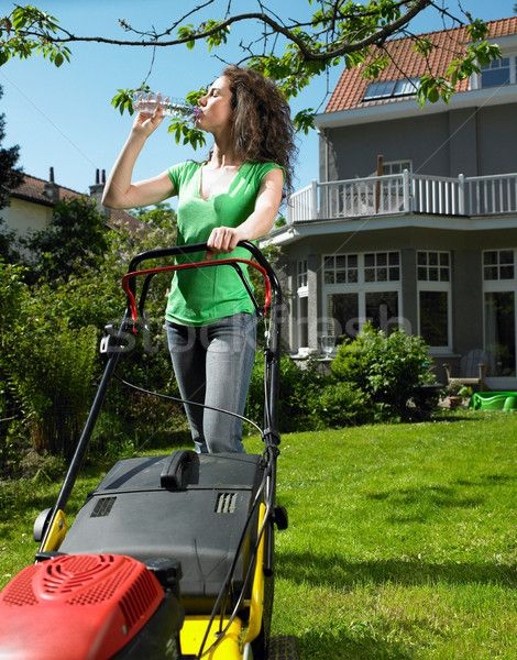 Woman mowing lawn in the sun stock photo (c) IS2 (#8547932)   Stockfresh