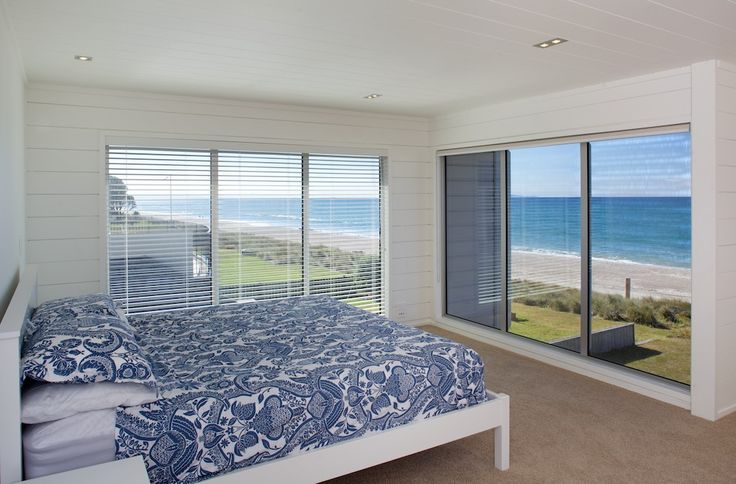 Views from the main bedroom of this Lockwood beach home are maximised with huge windows. All white interiors are ultra modern.