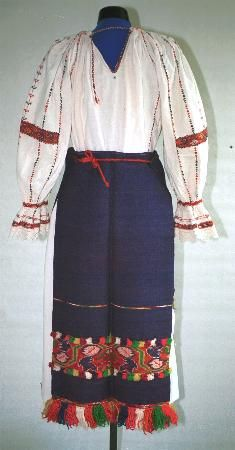 Women's costume from county of Maramureş, zone Lăpuş; White linen underskirt (poale) w/drawstring at waist. Front & back aprons (catrinţe) made of a single width of blue woven material. the front apron (prag) has wide band of red, yellow, green  woven horizontal rows, with red, yellow, green and white woollen fringes attached to the hem. back apron has a narrower band of co-ordinated woven decoration and fringes. Aprons are tied round the waist using narrow red cords called 'frimbii'.