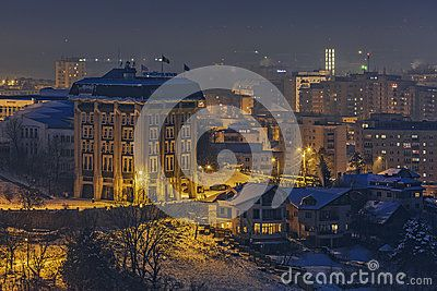 Brasov, Romania - 31 December, 2014: Tranquil winter nightfall cityscape with Transilvania University of Brașov, a public institution of higher education, ranked 1138 in the world in 2015.