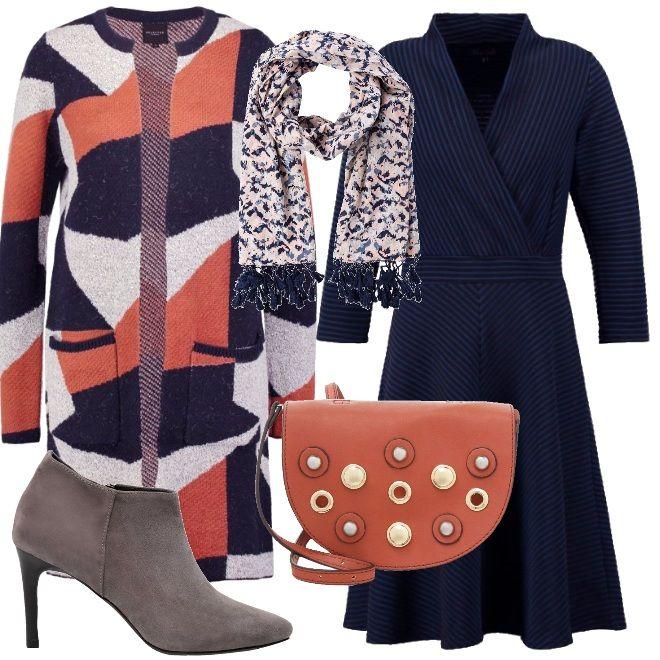Il vestito blu scuro con collo a scialle ha un gioco di righe che vi regalerà una taglia in meno e allo stesso tempo metterà in risalto le curve. Il soprabito ha una fantasia che mescola sapientemente il blu, il grigio e l'arancio, a completare l'outfit una sciarpa con nappine. Ai piedi boots dal taglio elegante grigi e una piccola tracolla arancione con applicazioni di perle ed occhielli in metallo.