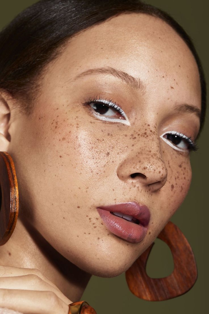 A model with freckles wearing large wooden hoop earrings, and white eyeliner around her eyes!