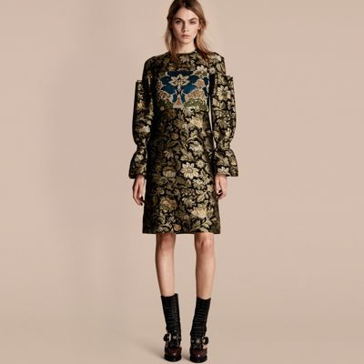 A shift dress in textured fil coupé with a floral pattern echoing antique tapestries. Reminiscent of period-style silhouettes, sleeves are sculpted using large gathers and bell cuffs for dramatic fullness. A band of sequins and beads, all individually sewn, creates graphic interest at the chest and back.