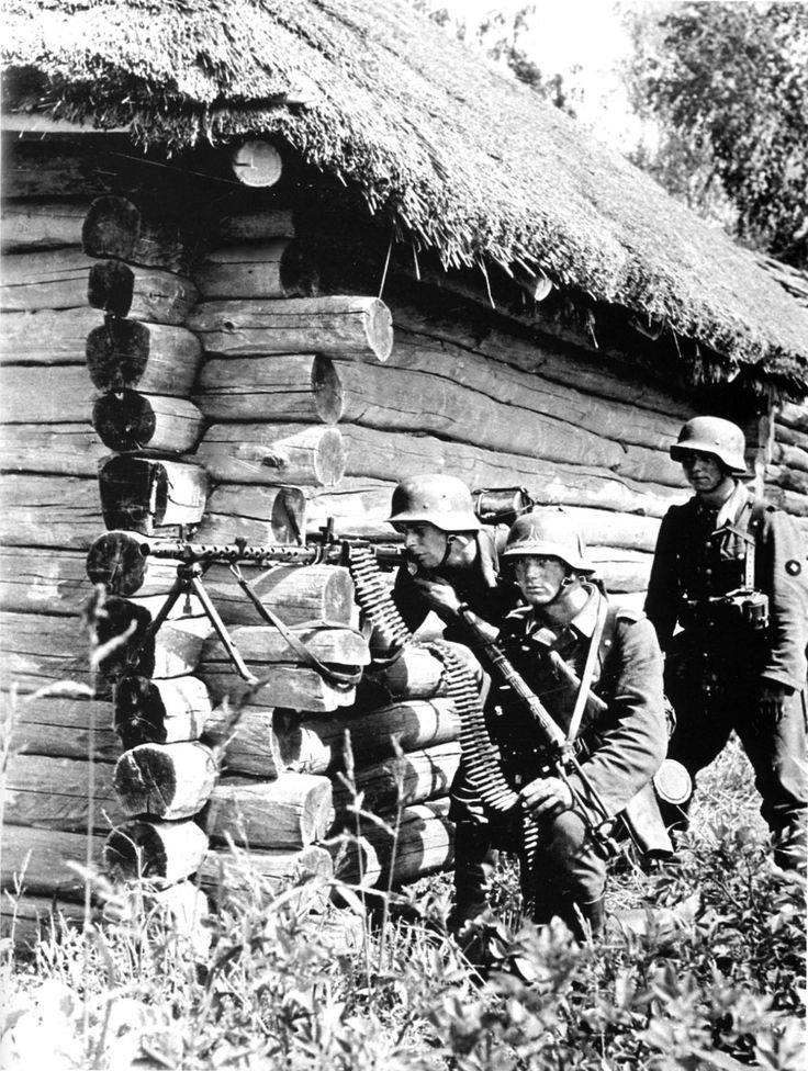 "Caption: ""German soldiers man an MG 34 (Maschinengewehr 34) recoil-operated machine gun, taking cover on the side of a house in Rahachow during the German invasion of the Soviet Union (Operation Barbarossa). Rahachow, Gomel Region, Belarus, Soviet Union. July 1941. """