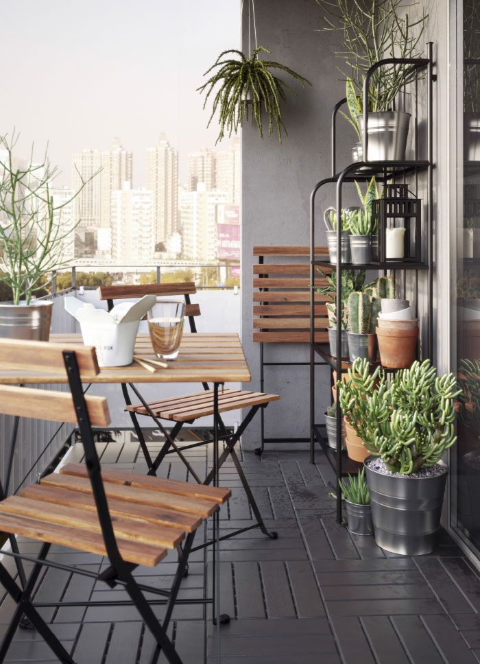 小さいベランダにアカシア無垢材の折りたたみ式のテーブルと折りたたみ式のチェアが3脚、脚の部分はブラックのスチール製。グレイのスチール製シェルフユニットにブリキ製の植木鉢に入った植物が置いてある。