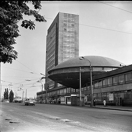 «Летучая Тарелка» на Лыбидской, теряющаяся в наши дни между новых застроек, - одна из самых известных достопримечательностей архитектурного модернизма на всем постсоветском пространстве. Ее необычная форма связана не столько с «космической», как с художественной, не менее инновационной утопией. В начале 1960-х годов архитектор Флориан Юрьев разработал проект светло-музыкального театра, и для реализации идеи синтеза искусств здание должно иметь характерную овальную форму. Проект был воплощен…