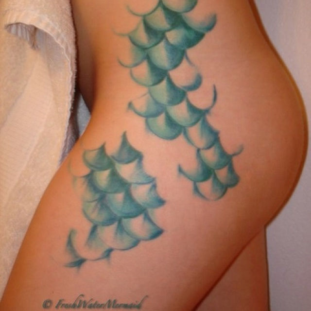 I want something similar. Green scales (as Ariel from the Little Mermaid) but one of the scales is from the rainbow fish. The story being that the last scale that the Rainbow Fish gave away was to Ariel so that she would always remember to share her wealth with those less fortunate than her.