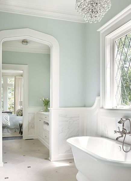 Chic master bathroom boasts upper walls painted gray blue and lower walls clad in marble ...