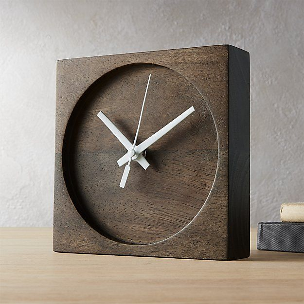 Shop square circle table clock.   Solid mango wood carves a freestanding dichotomy of shapes on this geometric table clock.  Revealing the active grain of the wood,squaregives way to recessed circle punctuated by gleaming aluminum hands.