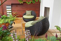 Outdoor garden room with oversized patio furniture chairs, Acanthus, wall, mixed landscaping hardscape materials, plants, fireplace, firepit, ferns for a private relaxing backyard sitting area, Astilbe, wooden fenced privacy wall, outside room