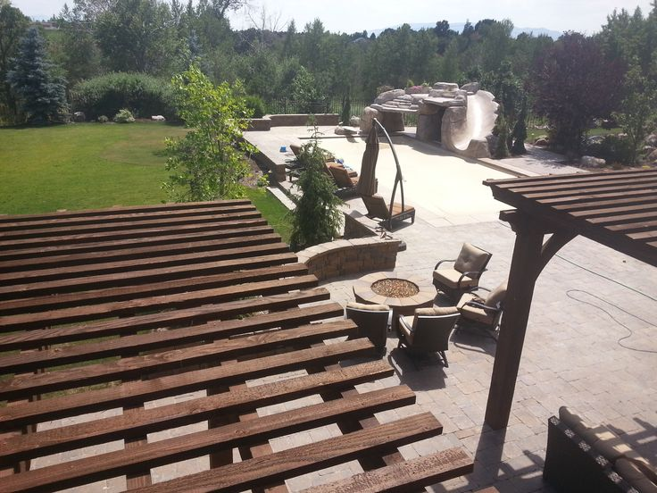 Top view of the Outside pergola in the backyard with a natural gas fire pit, Swimming pool, Gunite slide, diving and jumping faux rock and cave, diving board, Paver sitting walls in Alpine Utah