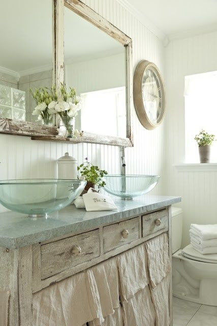 Save money by repurposing old tables for vanities and covering with remnant stone.  like the white paneling