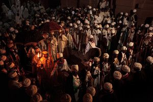 Deacons-walk-with-a-flame-in-a-procession-during-Christmas-celebrations,-Lalibela,-Ethiopia.jpg-Lalibela is also one of the main centres for celebrations of Christmas or 'Ledet' (for Ethiopians). Unlike Christmas in most of the world, the Ethiopian Orthodox Christmas falls on the 7th of January. The days leading up to the date bring pilgrims and visitors from the surrounding areas, as well as from outside of the country. The celebrations are held over two days and culminate in a…