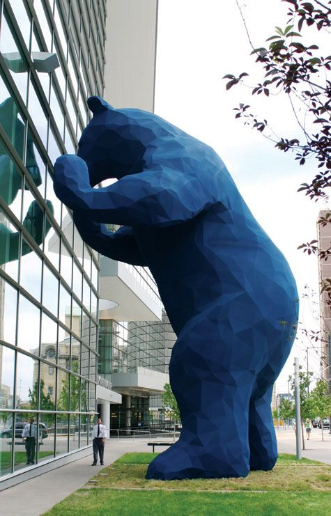 Sculpture of a big blue bear peeking through the windows of the Denver Convention Center.    I See What You Mean, 2005, Lawrence Argent, Composite materials