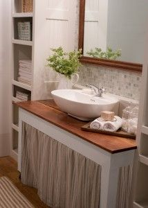 rip out the vanity and replace with a simple table, skirt, and table top sink.  also love the shelves