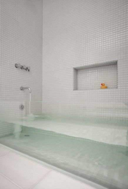 This custom designed bathtub has a clear front -- so unusual - would certainly open up a small space!