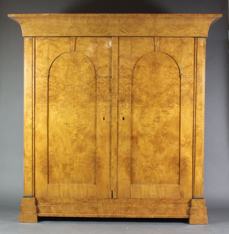 """Lot 1040, A handsome 19th Century Biedermeier armoire with moulded cornice, the interior fitted hanging space and shelves, enclosed by a pair of arched panelled doors with keystone decoration, raised on a stepped base 69""""h x 75""""w x 27""""d, est  £1500-2000"""