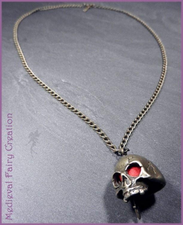"""Collier """"Crâne à la dague"""" : Collier par medieval-fairy-creation Collier court, crâne laiton aux yeux rouges transpercé par une dague. Crâne : 2cm environ. occasion : Halloween par exemple http://www.alittlemarket.com/collier/collier_crane_a_la_dague_-1882441.html"""