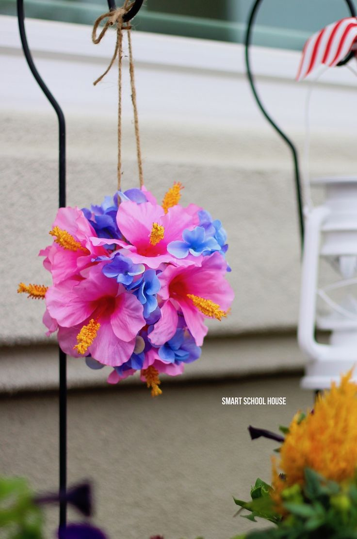 Tropical flower ball using hibiscus and hydrangea. Make these flower pomanders with wiffle balls in about 10 minutes!! Easy, stunning and so tropical looking! These would be excellent for a beach wedding too. You're never going to belive how quick and easy this DIY decor craft is.