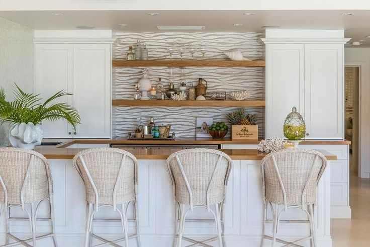 Charming built in bar features four light wicker barstools sat in front of a white paneled peninsula topped with wood countertops that continue around to a back wall holding two styled mounted wood shelves accented by a fois bois wallpapered backsplash and flanked by white shaker cabinets fitted with aged brass knobs.