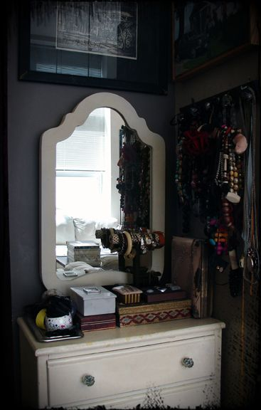 Necklaces, boxes, and mirror corner with artwork.