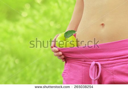Woman's fit belly with green apple and oversized pants, on green bokeh background
