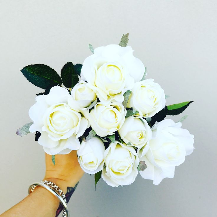 A beautiful bouquet of premium artificial white roses, that includes 9 stems of two different sized roses and foliage. 33cm in length.