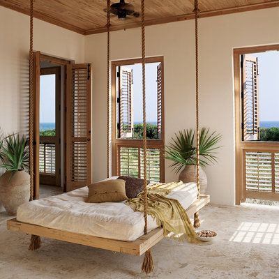 Off the first-floor master bedroom in this Asian- and Mediterranean-inspired abode in Rosemary Beach, Florida, the homeowner doubled her relaxation space by suspending a hanging bed. Its simple form—a wood palette topped with a mattress, pillows, and a th