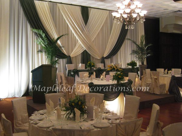 Toronto Wedding Decorations - Custom Backdrop and Head Table Draping Design by Mapleleaf Decorations in Olive Green and Ivory Satin and Palm plants for a tropical accent at Montecassino Hotel & Event Venue. Contact us for more info www.MapleleafDecorations.com
