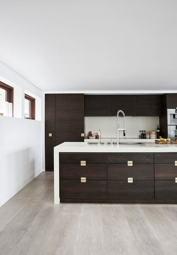 Kitchen from Simonsen and Czechura with cabinets in smoked oak, brass handles and a countertop in Corian.