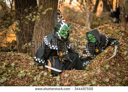 Two men in black cloaks with hoods and masks with guns goblins walk in the autumn park, carnival, disguise, masquerade, Halloween