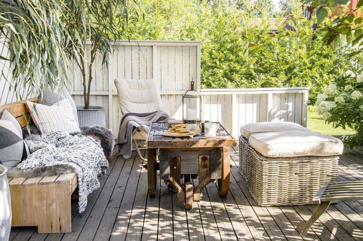 Mengder med myke tekstiler, grønne planter og røffe materialer preger terrassen. «Benken» består av tre teakstoler som er satt sammen, de kan også stå for seg selv. Stolen med trekk er alles favoritt, her er det førstemann til mølla. Piltrærne på hver side av benken er kunstige. Krakkene av kurv med myke sitteputer er også med på å skape et avslappet uttrykk. Alt fra Bolina.