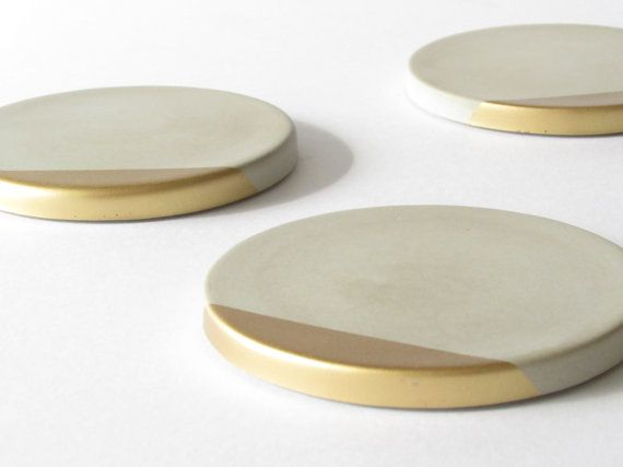 Set of concrete coasters with metallic gold edge and sealed with a semi-gloss topcoat. - 4.25 inches (10.8 cm) in diameter. - Each coaster has four