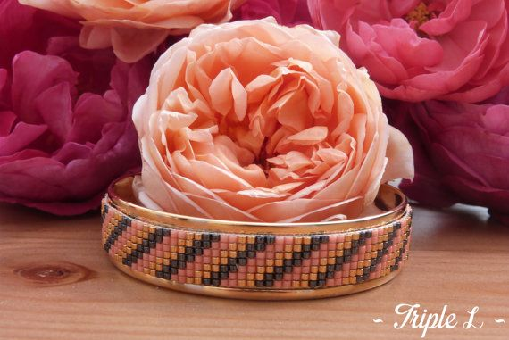 ~ DESCRIPTIF ~ Ce bracelet manchette LÉRIA est composé dun tissage fait main avec des perles de verre Miyuki et dune manchette en laiton doré. Couleurs des perles : saumon - noir métallisé - doré. Dimensions : 1.9 cm de large. ~ MATERIEL UTILISE ~ - Perles de verre japonaises Miyuki - Manchette en laiton doré - origine : Europe  ~ ENVOI ~ Les bijoux sont envoyés en courrier suivi dans une enveloppe en papier bulle et soigneusement emballés.  ~ PRECAUTIONS DUSAGE ~ Ce bijou est fait à la main…