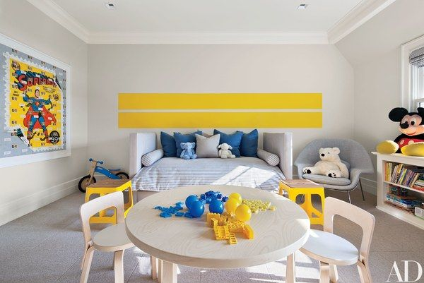 In a children's room, racing stripes painted in a Benjamin Moore yellow make a graphic statement; the trundle bed is by Jonas, the yellow stools are from CB2, the Alvar Aalto table and chairs are from M2L, and Knoll's Eero Saarinen Womb chair is from Design Within Reach.