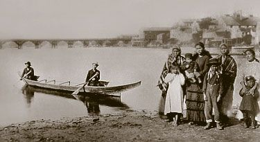 This is a black and white photograph of two Songhees paddlers in a northern-style canoe at James Bay, with Songhees people standing on shore.
