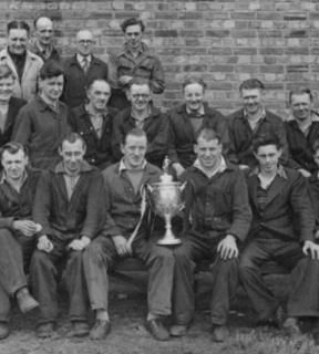 Crook Town captain, Bobby Davison, showing the FA Amateur Cup off to his workmates at Marshall Richards Machine Company