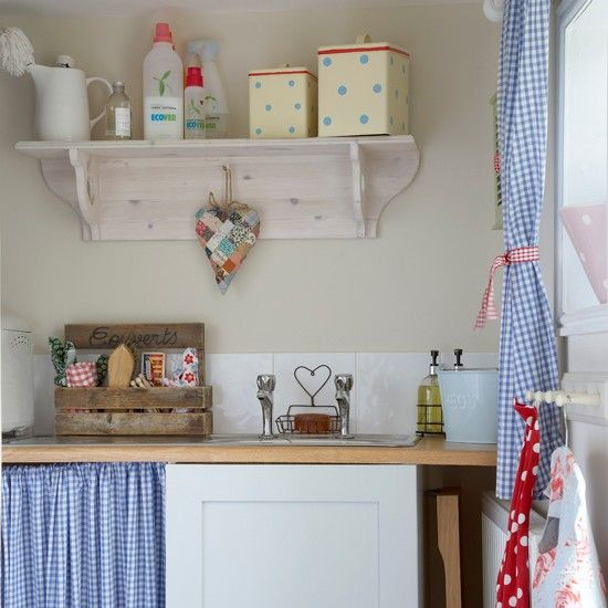 By using the same fabric for the windows and the under-sink unit, this utility space fits into its environment with ease. Pretty wooden shelves and peg hooks add open storage for keeping laundry equipment within easy reach.