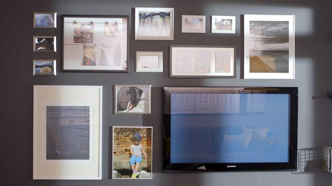 APRÈS : Le mur principal a été revêtu d'un gris charbon, où plusieurs cadres à photos disparates ont été accrochés autour de la télévision, pour lui permettre de se fondre dans le décor et de s'effacer légèrement à travers les souvenirs.