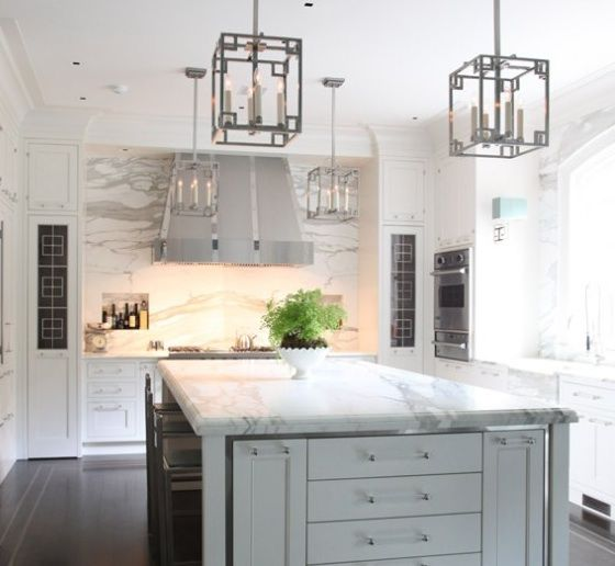 Two-tone kitchen with gray kitchen island, floor to ceiling white kitchen cabinets, marble slab countertops & backsplash and polished nickel pendants.