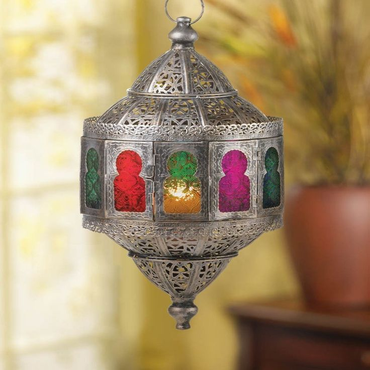 """Rustic Moroccan Hanging Lantern.    You simply wont find a more stunning candle lantern than this! Gorgeous silver metal is shaped like an exotic treasure featuring intricate patterns and cut work that lets the light of a candle shine through. The central windows cast a rainbow of hues that will create a fantastic ambiance in any room of your home.  Item weight: 3.60lbs Item dimensions: 10.00"""" W x 19.50"""" H x 10.00"""" L Materials: Metal Glass"""