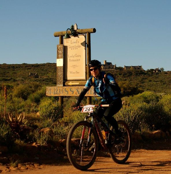 Rider cycling past Lord Guest Lodge. A beautiful lodge for your weekend accommodation.