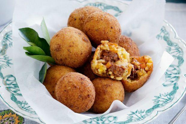 Οι ροδοκόκκινες κροκέτες που θυμίζουν πορτοκαλάκια (arancini): κλασικό οικογενειακό φαγητό της Σικελίας, που γίνεται με τα υπόλοιπα προηγούμενων ημερών. Πιάτο που το είχαν επινοήσει τα χρόνια της στέρησης οι πολυμήχανες νοικοκυράδες για να χορταίνουν την οικογένειά με νόστιμο και φτηνό φαγητό.