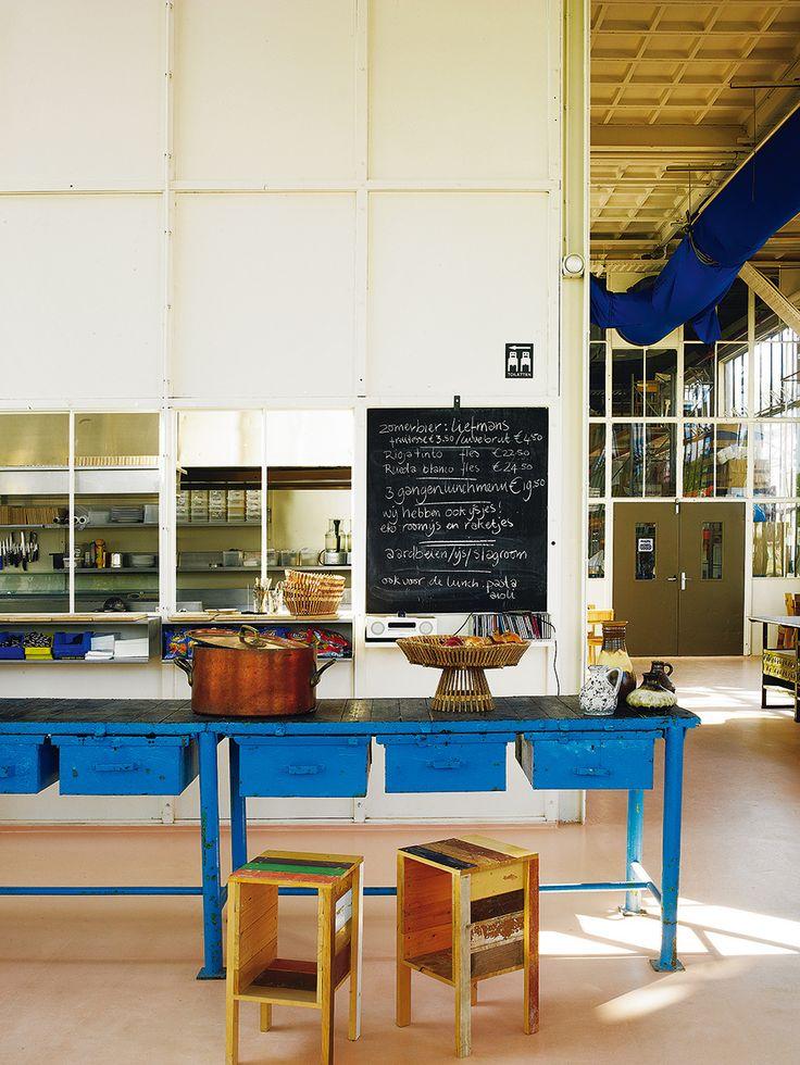 Gran azul - AD España, © Pablo Zamora Junto a la barra del restaurante, mesa de taller con cerámica vintage. Frutero y mesitas de Eek.
