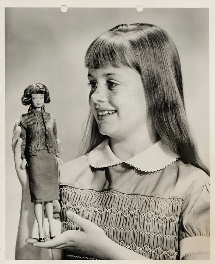 """Promotional photograph of the very earliest Midge doll, showing the prototype smiling face with exposed teeth and rather startled eyes, from a press kit by the manufacturer, United States, 1963, by Mattel, Inc. The accompanying press statement describes Midge as Barbie's """"best girl-friend,"""" and presents her as a """"lovable, snub-nosed, freckle-faced 'girl next door' type,"""" a very similar line of ad copy used by the recently released and moderately successful Tammy doll by Ideal Toy Corp."""