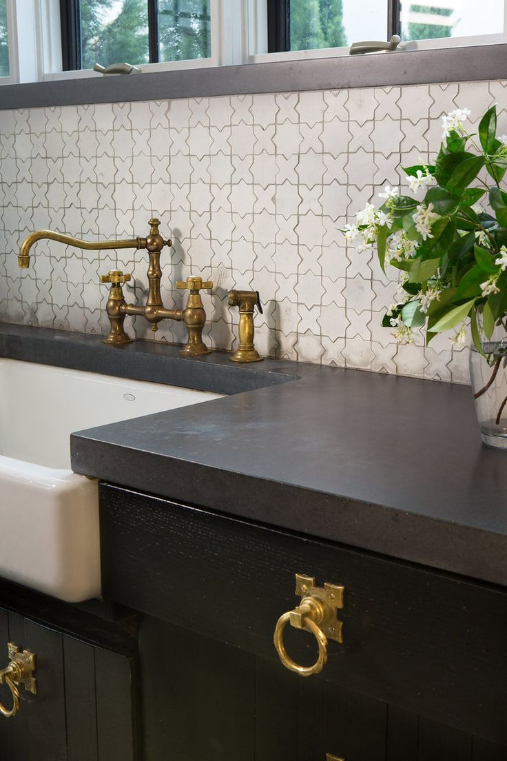 Alys Beach kitchen detail, black counters paired with brass hardware and Moroccan tile backsplash.